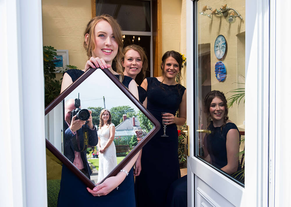 This is one of my favourite fun shots from the wedding which was taken at the bride's house. I'd just finished photographing the bride when I looked round to see one of her bridesmaids holding up a mirror for her to see herself in.