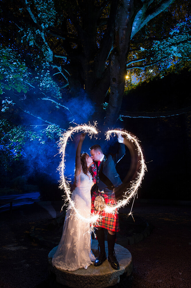 Sparkler photographs are always fun to do at weddings such as this one under the Kissing Tree at the Brigadoon Hotel, Alloway, Ayrshire