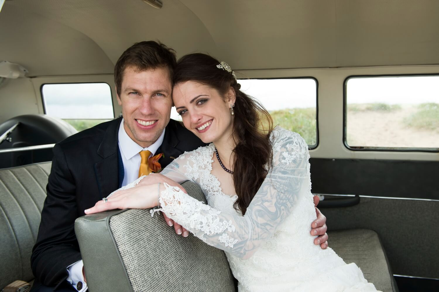 Relaxed Portrait of Bride and Groom inside VW Campervan